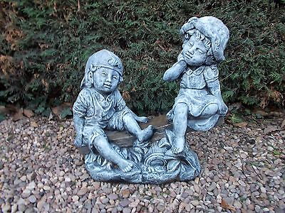 Boy and girl on see-saw concrete garden ornament