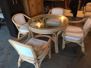 wicker dining table with 4 white padded chairs