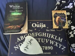 Ouija board with a Wicca hand book and some tarot cards