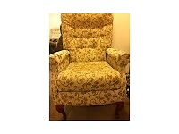 Armchair, beige patterned. Upright, with wooden legs.
