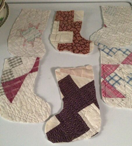Six antique vintage quilt blocks  cut into Christmas stocking shapes.
