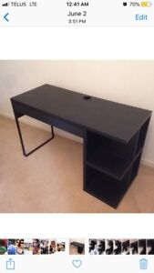 Black IKEA computer desk with drawer and side compartments