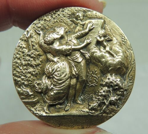 ANTIQUE BRASS PICTURE BUTTON ~ COUPLE KISSING BEFORE A STATUE WITH CHERUBS