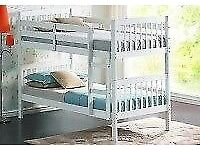 White wooden bunk beds with one brand new mattress still in plastic.
