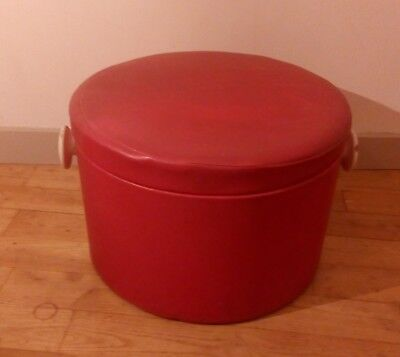 A vintage pouffe with wooden handles