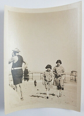 Snapshot Photograph Two Girls Walking on Beach Men in Bathing Suits Ocean 1920s