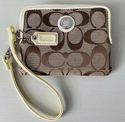 Small, cute COACH wristlet purse with classic monogram design and cream strap