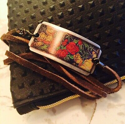 Bracelet leather wrap around vintage floral metal plate.