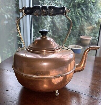 Antique copper kettle with wood handle on tripod feet