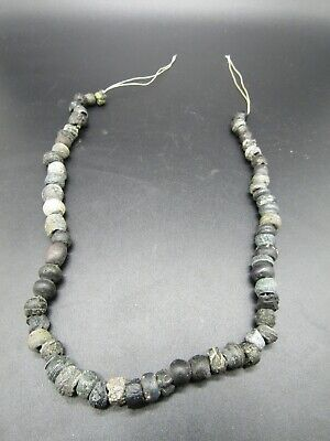 63 Romano Egyptian black glass beads on sting, 2000 years old