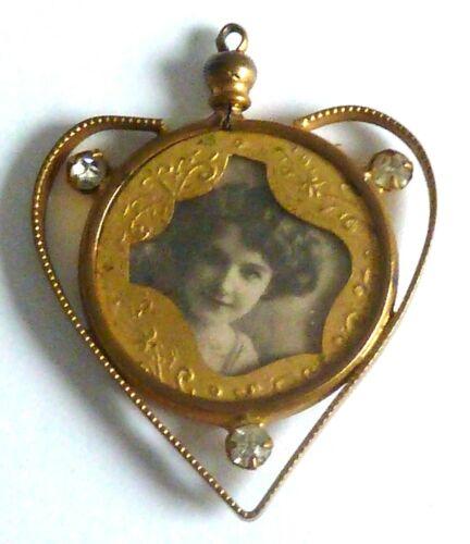AN EDWARDIAN GOLD TONE HEART SHAPED DOUBLE SIDED LOCKET PENDANT