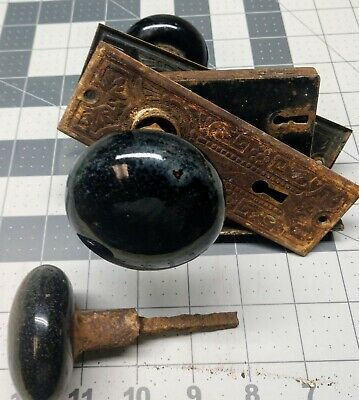 Black Porcelain Door Knobs With Hardware and a Third Knob