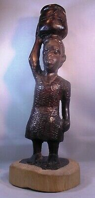 African Makonde Carving of tribal woman carrying water on bark stand. Ebony