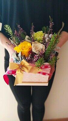 Composizione di fiori con rose stabilizzate, erica, pino e garofani