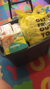 A bin of newborn diapers and boy clothes