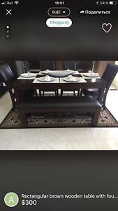 Rectangular brown wooden table with four chairs and bench