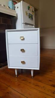 Freshly painted white antique bedside drawers