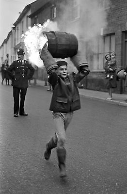 A boy runs through the street carrying a burning barrel in 1963. PA