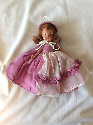 Storybook Doll Bisque Body, Frozen Leg, Red Head Purple Dress And Bonnet