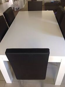 White dining table and 8 black dining chairs Beaumont Hills The Hills District Preview