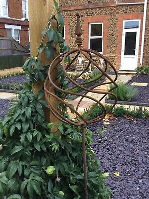 Rusty metal garden sculpture obelisk ball on post
