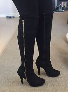 Tall black boots with zipper.