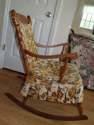 Antique wooden rocking chair, medium wood color, orange and brown cushions ()