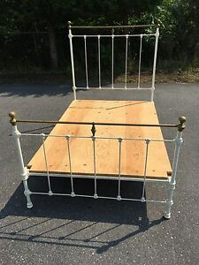 Antique metal bed frame with brass highlights
