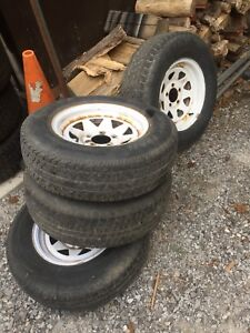 """14"""" 5 bolt trailer rims and tires."""