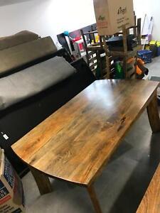 Vast interior mango hardwood dining table with chairs.