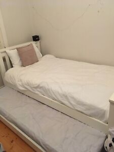 White wooden bed frame with trundle