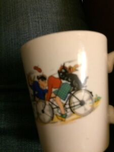 Children's small mug with children in bicycles and a dog