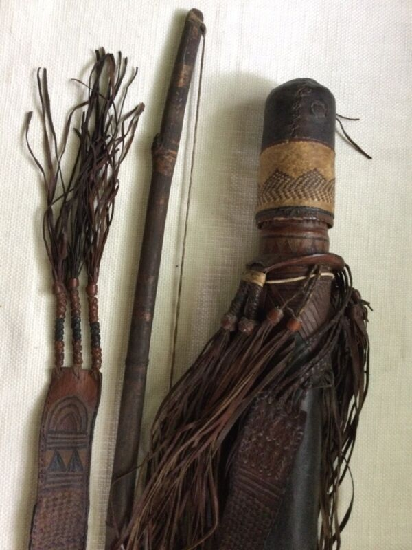 Ethnographic leather and snake skin quiver with arrows and bow.