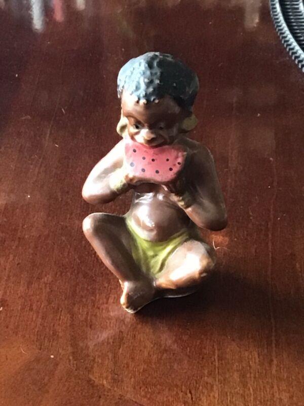 Vintage Antique Black Americana Porcelain figurine Eating a watermelon.