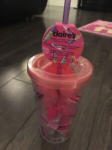 Cup filled with nail polish, lip balm, nail file and shower pouf