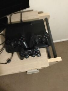 PS3 console with 3 controllers and a charger
