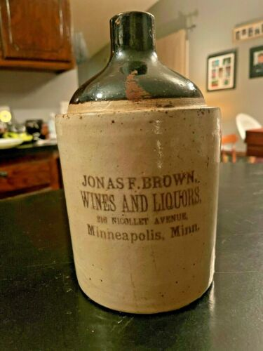Vintage Crock Liquor Jug with Advertising, 1/2 Gallon, Off-white with Brown Top.