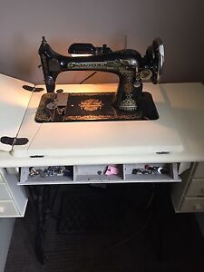Antique singer treadle sewing machine with cabinet.