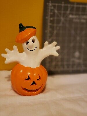 Ceramic ghost popping out of pumpkin with surprise face
