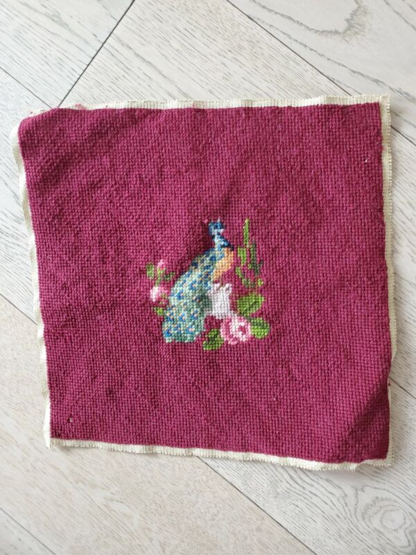 Completed finished wool needlepoint of a peacock; burgundy background
