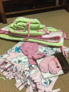 Various baby clothes, blankets and crib bumper pad set.