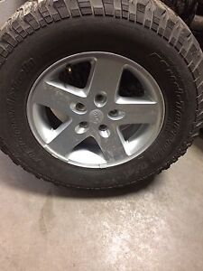 A set of 4 tire and rim of a jeep wrangler unlimited