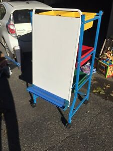Dry erase easel with whiteboard, paper hooks, and storage