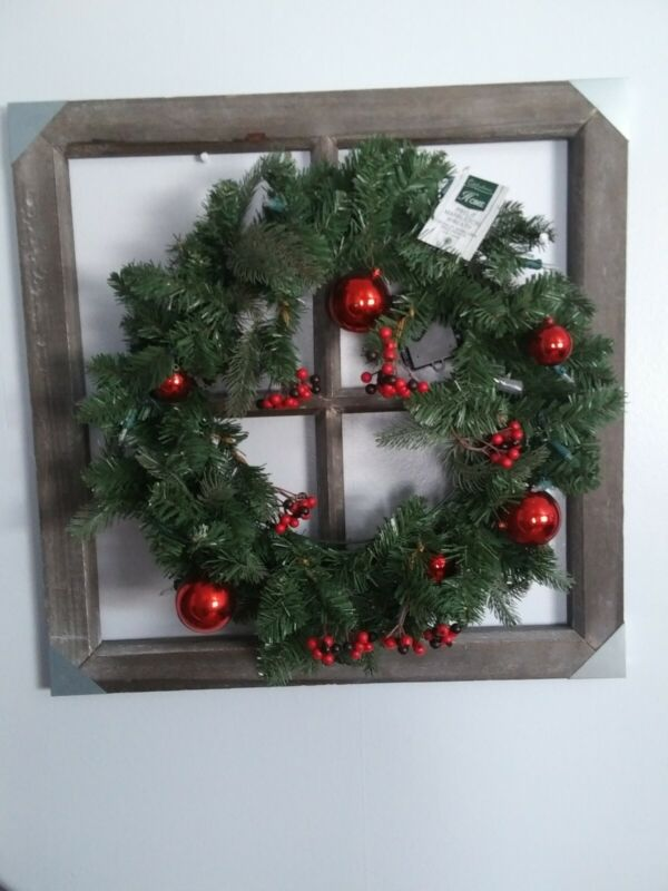 Beautiful wreath on wooden window red ornaments lights up wih batteries