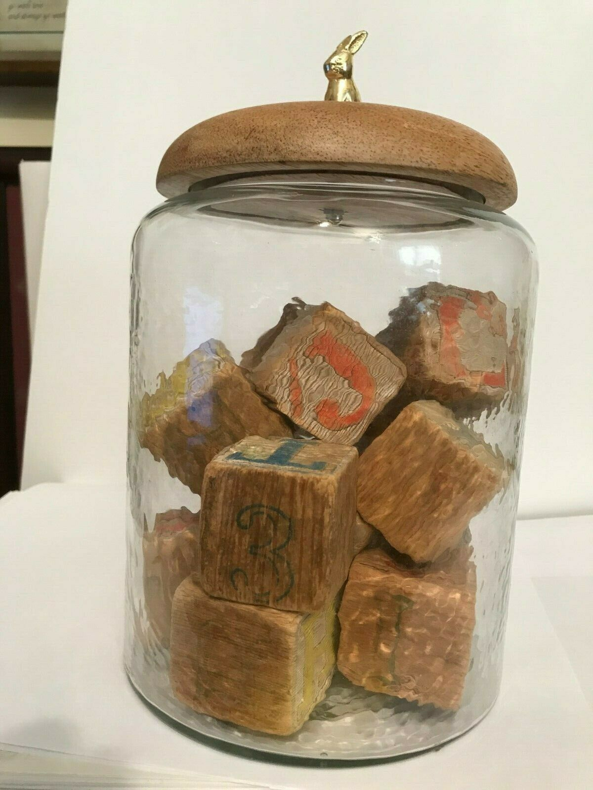 Rippled Glass Jar With 14 Vintage Wooden Blocks Inside With A Rabbit on Top