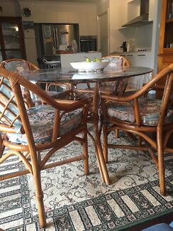 Beautiful glass-top cane dining set with cushioned chairs as new