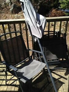 Three patio chairs and umbrella