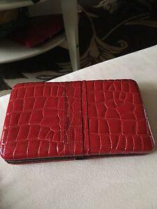 Portefeuille rouge rigide à compartiments.