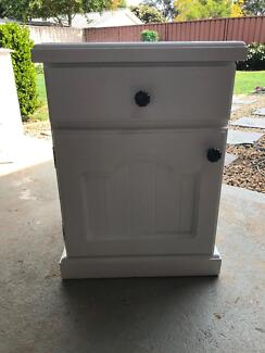 White bedside chest.