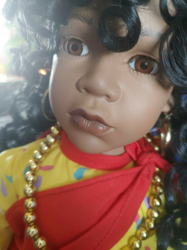 African American porcelain and cloth doll with colorful clothes